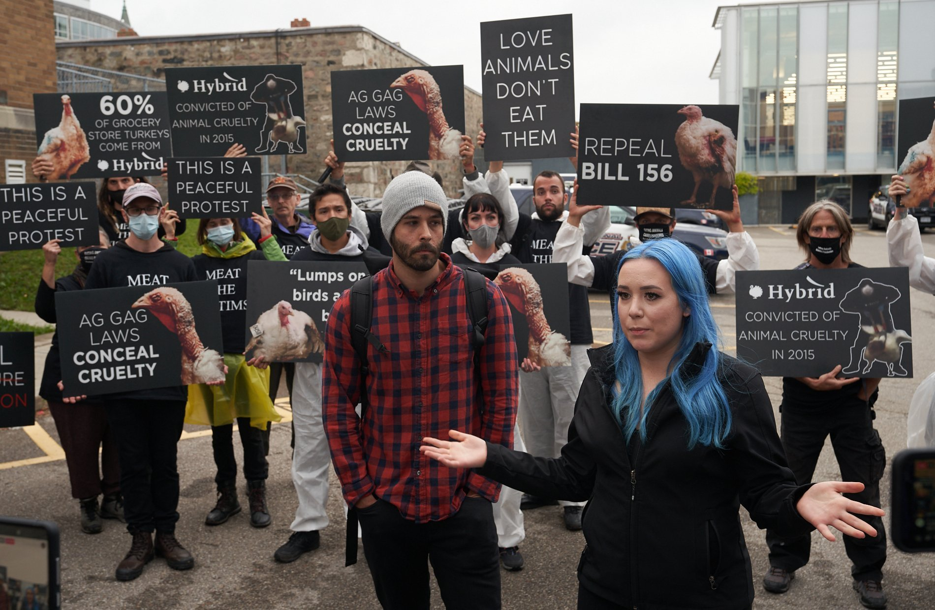 Amy Soranno (right) and Nick Schafer stand in front of supporters after being released from Waterloo Region police custody. Both were arrested and charged before a planned sit-in at a turkey farm on Oct. 3, 2021.