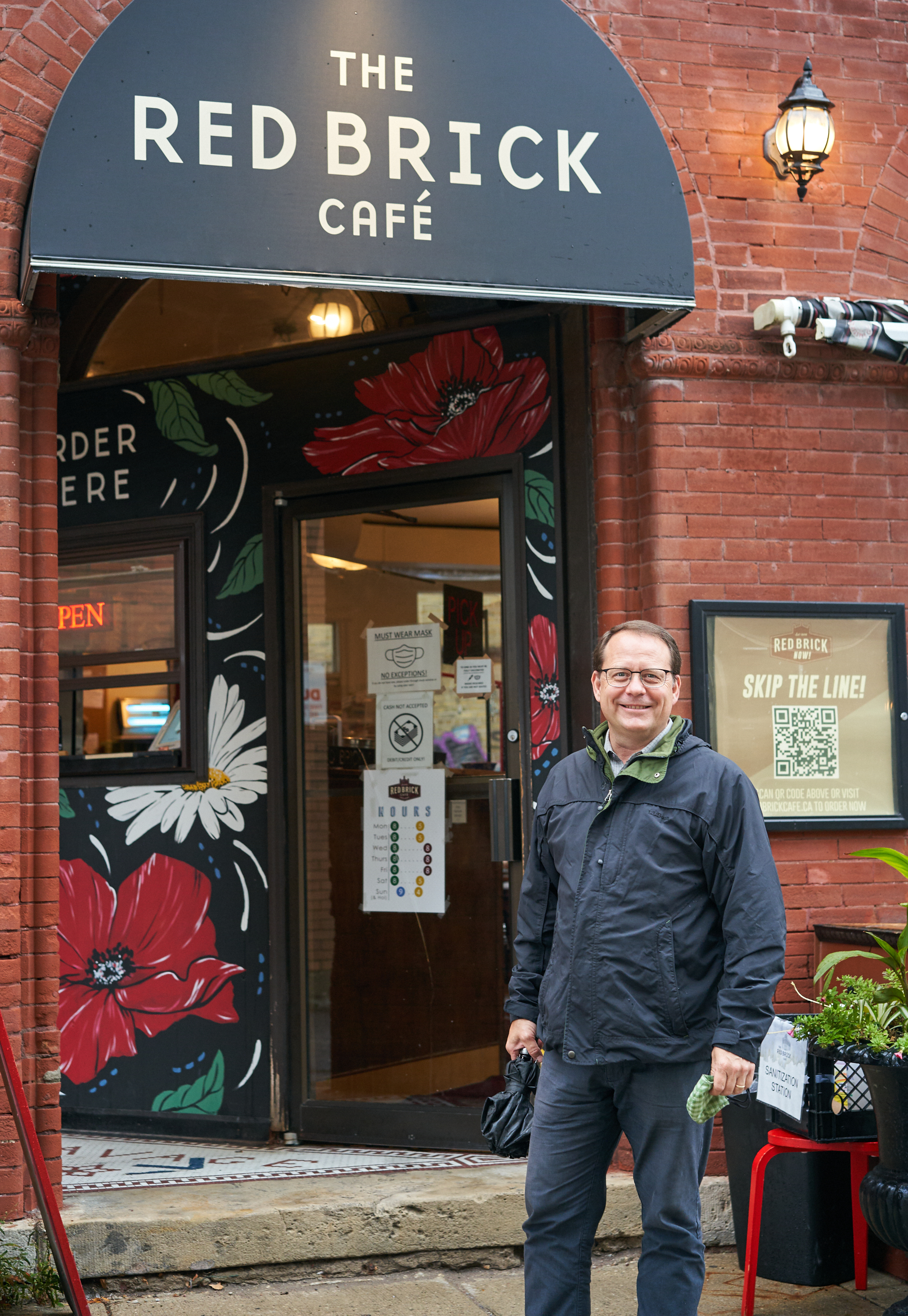 Guelph MPP Mike Schreiner stands outside the Red Brick Cafe in Guelph, on a rainy Wednesday afternoon.