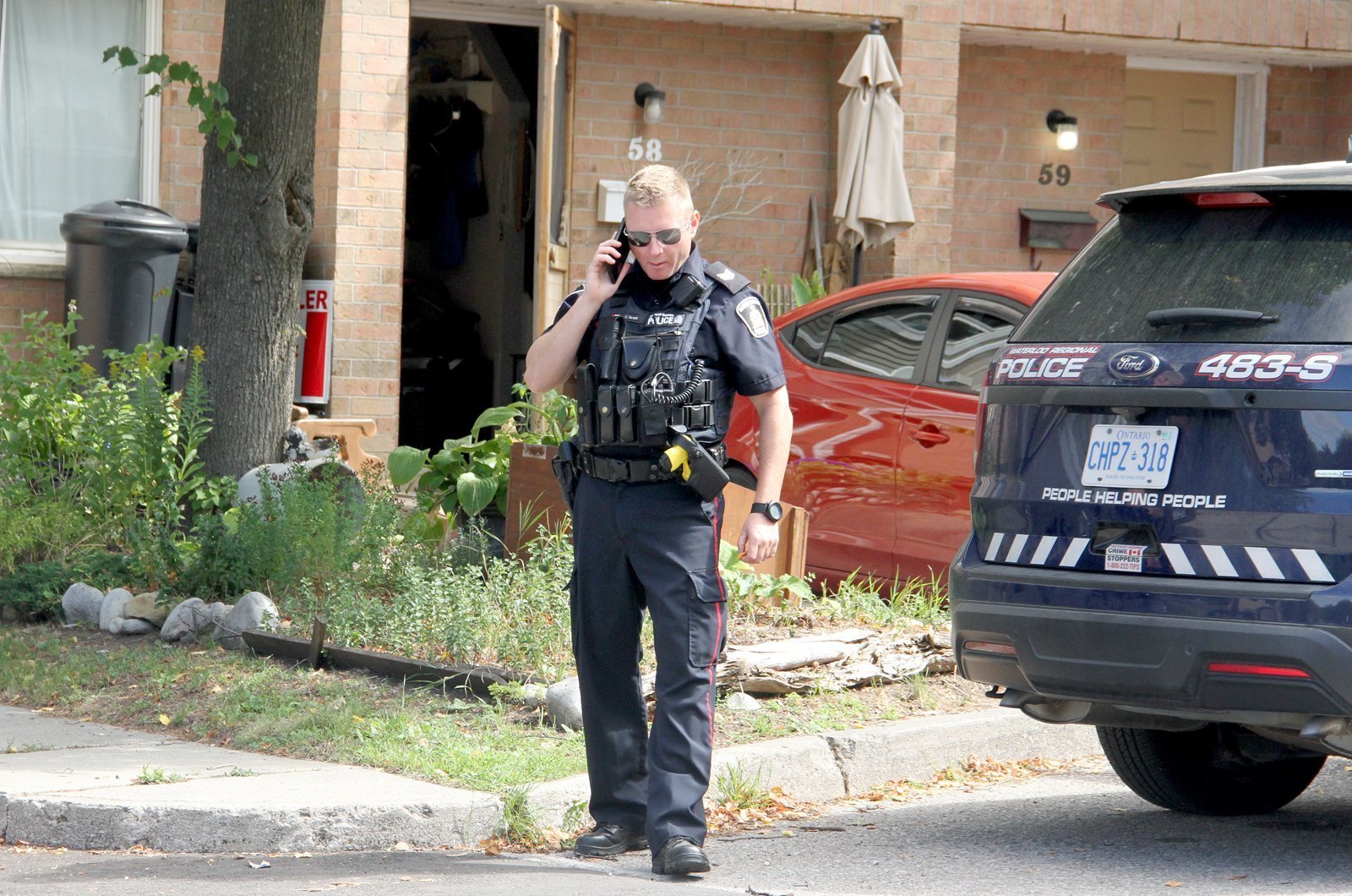 A Waterloo region police officer outside unit 58 of a Queen Street West in Hespeler residence where the murder took place.