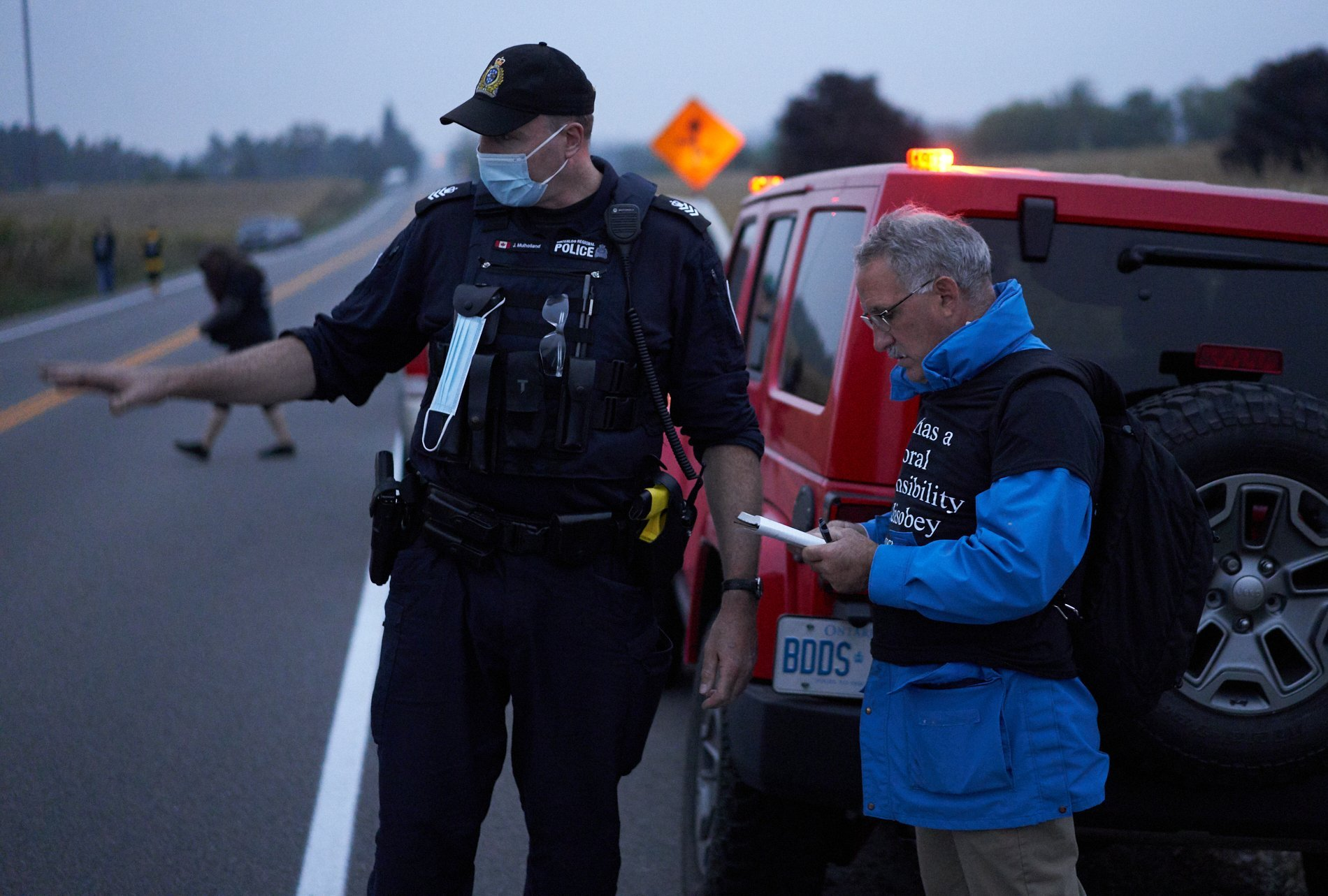 Dan Moskaluk (right) is a retired RCMP officer turned activist. He said he helps groups communicate with police while ensuring police behave the way they are supposed to. Here he is speaking with Staff Sergeant J. Mullholland about putting tents away from the road.