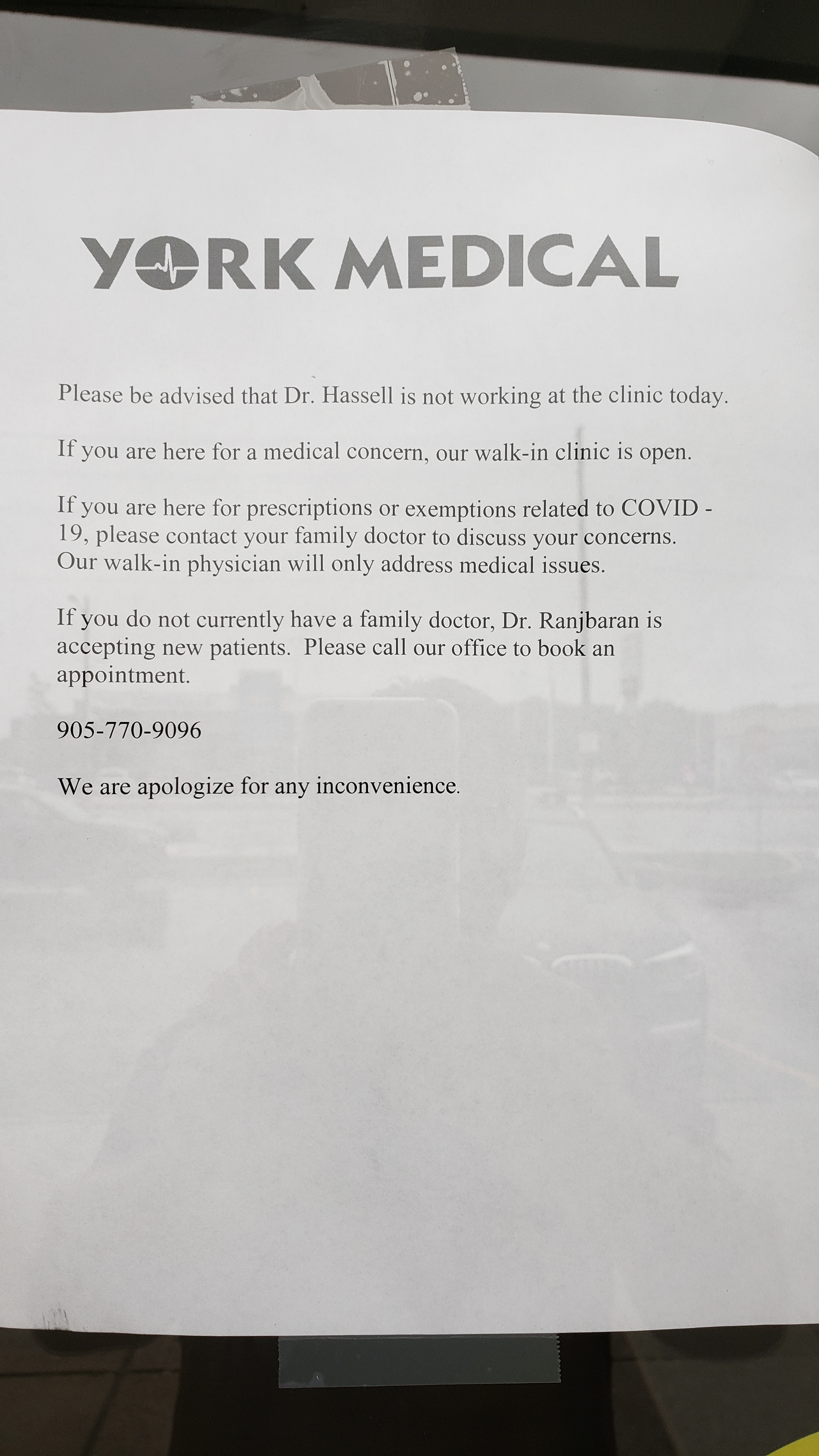 A piece of paper posted in a window advising people that a doctor was pausing his practice